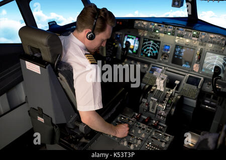 High angle view of young male pilot switching control while sitting in airplane cockpit - Stock Photo