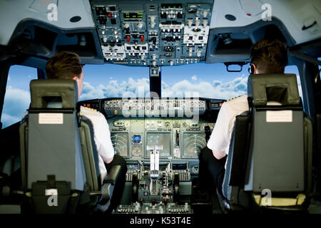 Rear view of co pilots sitting on seat in cockpit while flying airplane - Stock Photo