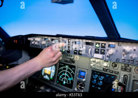 Cropped hand of young male pilot switching control in airplane cockpit - Stock Photo
