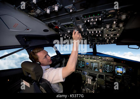 Handsome young pilot switching controls in airplane cockpit - Stock Photo