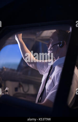 Side view of male pilot switching control in airplane cockpit seen from window - Stock Photo