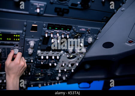 Cropped hand of male pilot switching control in airplane cockpit - Stock Photo