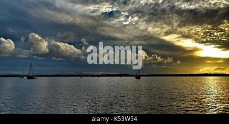 Threatening dark Cumulonimbus clouds in golden cloudy sunset seascape with sea water reflections. Photographed on - Stock Photo