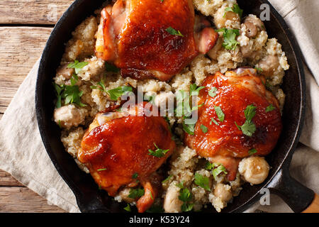 One pot: fried chicken thighs with quinoa and mushrooms close-up on the table. top view from above horizontal - Stock Photo