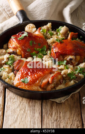 Tasty fried chicken thighs with a quinoa and mushrooms close-up in a frying pan. vertical - Stock Photo