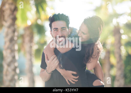 Portrait of happy young man giving his girlfriend a piggy back ride - Stock Photo