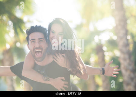 Portrait of happy man with spread arms giving his girlfriend a piggy back ride - Stock Photo