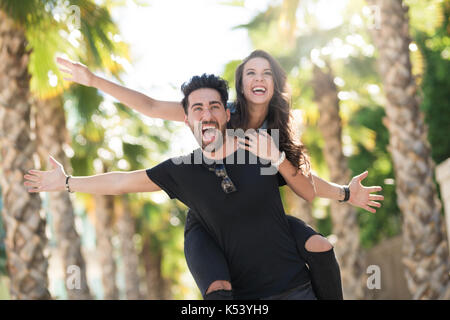 Portrait of man giving his girlfriend a piggy back ride with spread arms - Stock Photo