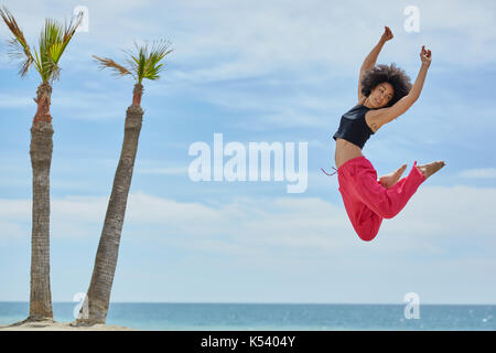 Portrait of young pretty sportswoman dancing jumping on beach - Stock Photo