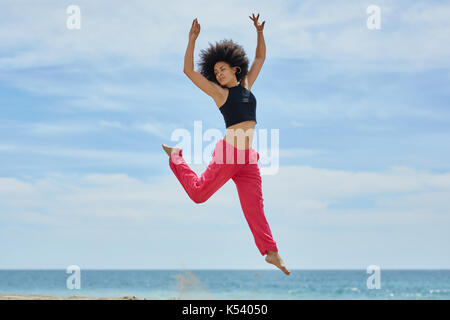 Portrait of young pretty sportswoman jumping on beach raising hands - Stock Photo