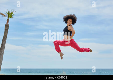 Portrait of young sportswoman jumping on beach with hands on waist - Stock Photo
