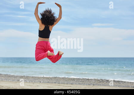Back portrait of young afro american dancer jumping on beach - Stock Photo
