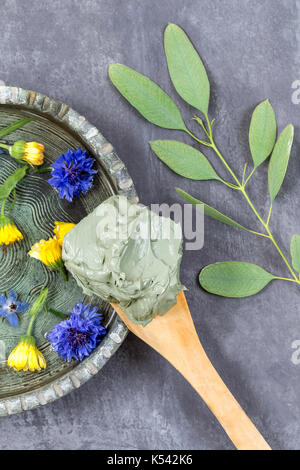 cosmetic clay and flower and branch of eucalyptus, for spa treatments, in ceramic plate mud on wooden spoon on grey - Stock Photo