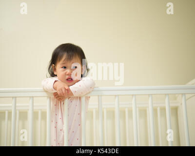 Baby girl crying in cot bed - Stock Photo