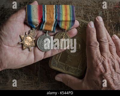 Bar of Three First World War Service Medals and hands of the photographer - Stock Photo