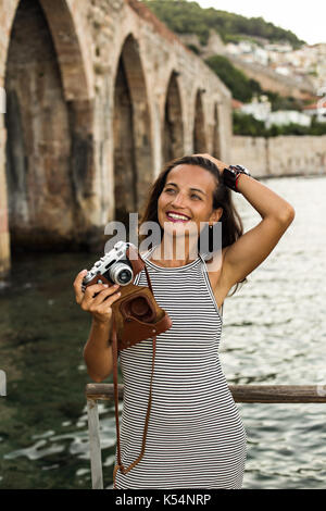 Smiling traveller woman with vintage camera wearing black and white striped dress looking away and standing against - Stock Photo