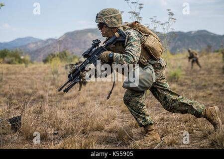 A U.S. Marine with 3rd Battalion, 7th Marines, runs during a simulated squad ambush phase of the 1st Marine Division - Stock Photo
