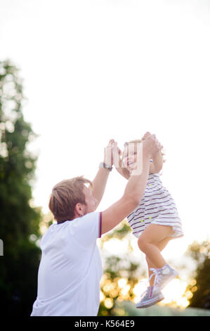 Young dad is playing with a charming little daughter. - Stock Photo