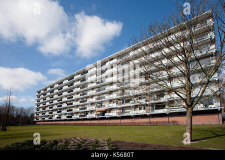 Apartment block from the 70's in a green environment. At the moment a lot of the apartments are used as social housing - Stock Photo