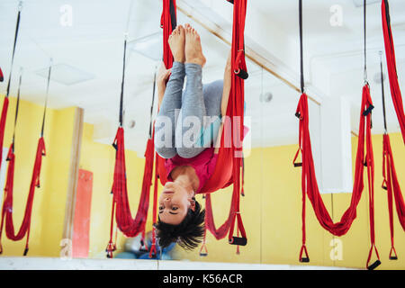 Young women doing yoga exercise or aerial yoga antigravity in the studio. - Stock Photo