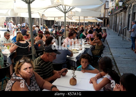 Tourists and local people sit outside at restaurant tables in the main square in Guimaraes, Portugal August 22, - Stock Photo