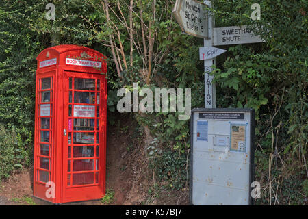A disused public telephone box housing books for exchange between people on an informal basis. This one stands outside - Stock Photo