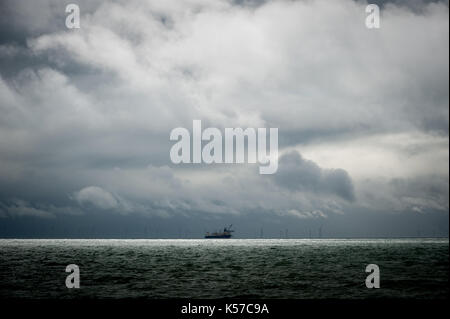 Dramatic clouds fill the sky out at sea over the construction site of the Rampion Wind Farm. Worthing, West Sussex, - Stock Photo
