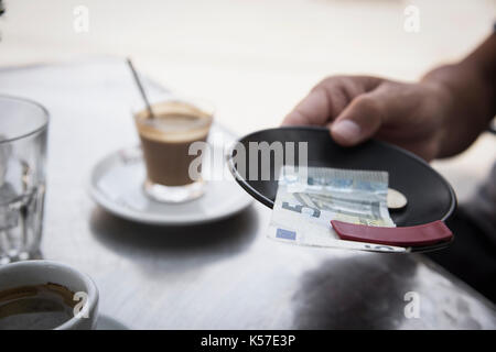 closeup of a young man sitting at a table in the terrace of a cafe paying the bill with a five euros banknote and - Stock Photo
