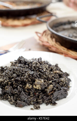 closeup of a plate with spanish arroz negro or black paella, made with squid ink, on a table set for lunch, next - Stock Photo