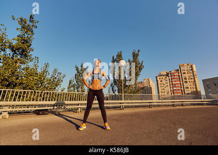 A girl runner stands on the road in the city - Stock Photo