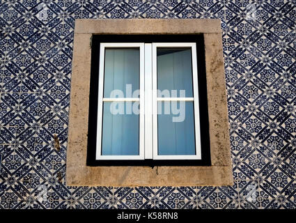 Decorative tiles surround a window on a residential building in Cascais, Portugal August 27, 2017. © John Voos - Stock Photo