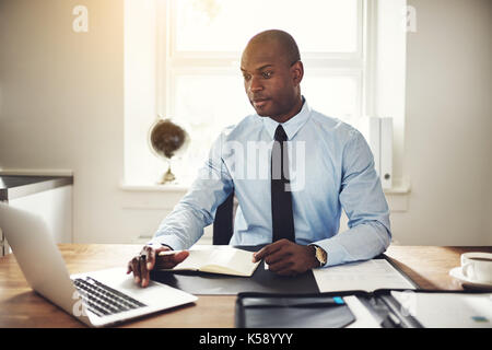 Focused young African businessman wearing a shirt and tie sitting at his desk in an office working online with a - Stock Photo