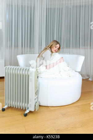 Young woman trying to warm up next to the radiator - Stock Photo
