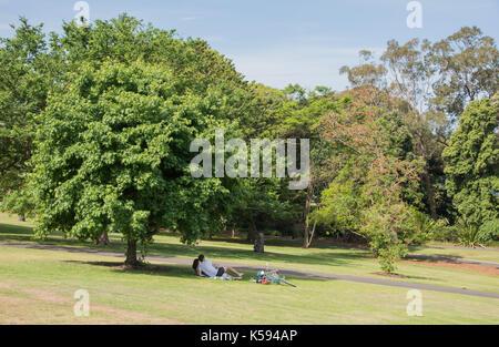 SYDNEY,NSW,AUSTRALIA-NOVEMBER 20,2016: Couple lying down under the shade of a tree with bike at the Royal Botanic - Stock Photo
