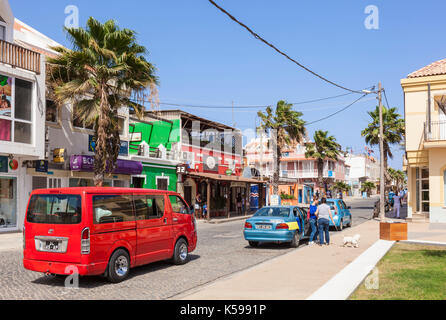 SAL Local taxis and aluguer or shared car driving down the main street, Rua 1 de Junho, Praca Central, Santa Maria, - Stock Photo