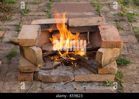 Flames burning wood in stove made from brick improvised on the floor - Stock Photo