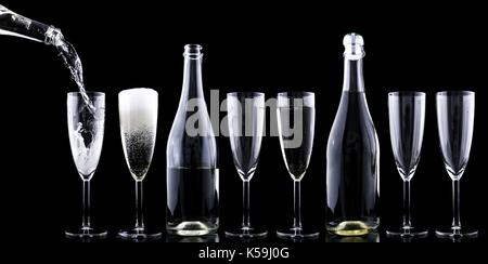 Champagne being poured into a glass on a black background - Stock Photo