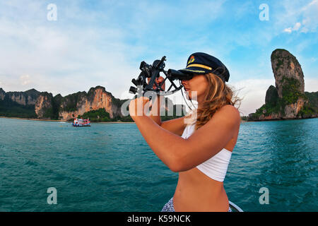 Young captain woman in cap on deck of sailing yacht taking sight in sextant to measure boat altitude position in - Stock Photo