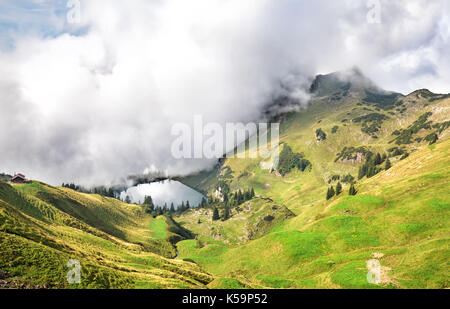 dense fog starts to cover alpine lake Seealpsee - Stock Photo