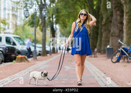 attractive young woman walks with a pug at the leash on a footpath in the city - Stock Photo