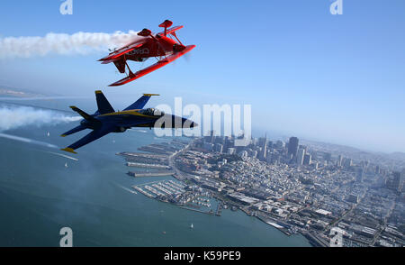 US Marine Corps Major Nathan Miller fly his F/A-18 Blue Angel #5 jet in position near Sean Tucker's Oracle Challenger - Stock Photo