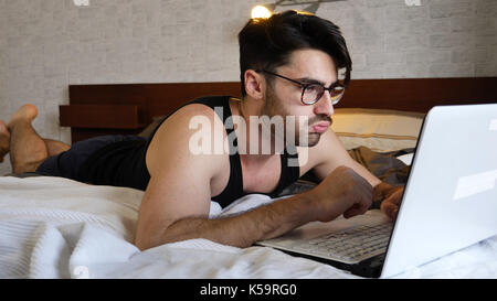 Young Man Doing Homework on Laptop in Bedroom - Stock Photo