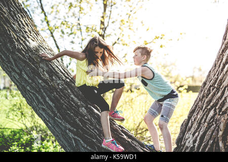 Portrait of a girl on a tree with his friend - Stock Photo