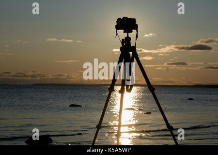 Camera with tripod over sunset near sea water - Stock Photo