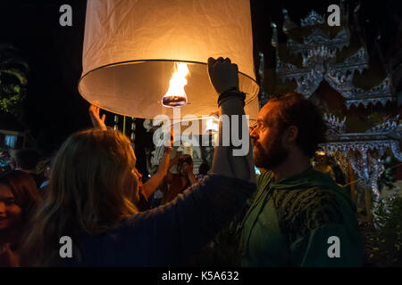 CHIANG MAI, THAILAND - 12/30/2015: Tourists release floating lanterns at a Buddhist temple on New Year's Eve in - Stock Photo