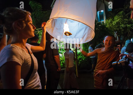 CHIANG MAI, THAILAND - 12/30/2015: A Buddhist monk and a tourist release a floating lantern at a temple on New Year's - Stock Photo