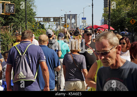 Crowds of tourists walk over Brooklyn Bridge on a sunny Labor Day holiday - Stock Photo