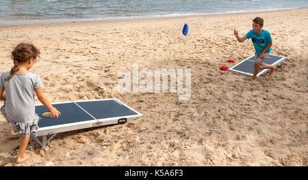 Children playing bean bag toss, cornhole, game on the beach. - Stock Photo