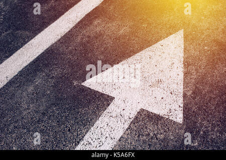 Moving in the right direction, white arrow symbol as traffic sign on asphalt road for motion directing toward the - Stock Photo