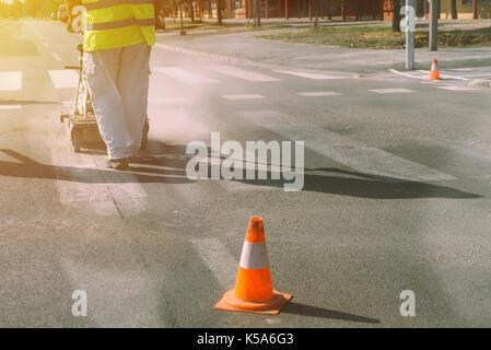 Worker is painting zebra pedestrian crosswalk lines on asphalt surface - Stock Photo